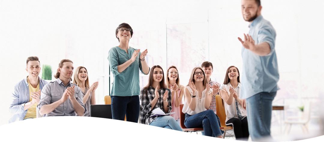 Symbolbild Vortragender erklärt, Teilnehmer der Schulung klatschen, eine Frau steht, andere Teilnehmer sitzen