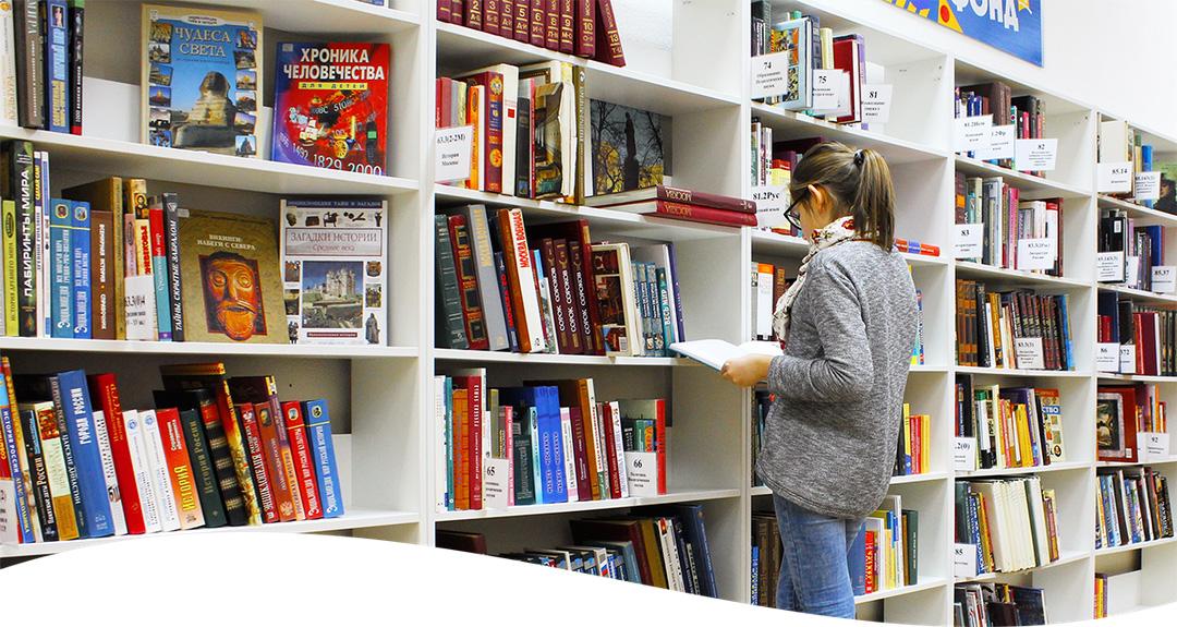 Symbolbild einer Frau mit Lesebrille, vor einem Bibliothekenregal, hält und liest ein Buch