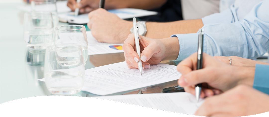 Symbolbild Ausschnitt von schreibenden Händen von Schulungsteilnehmern auf Schulungsunterlagen