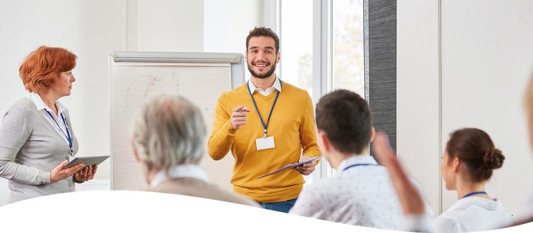 Symbolbild weibliche und männliche Vortragende bei einer Schulung, vordere drei Teilnehmer sichtbar